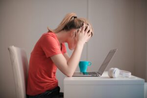Woman looking at laptop stressed